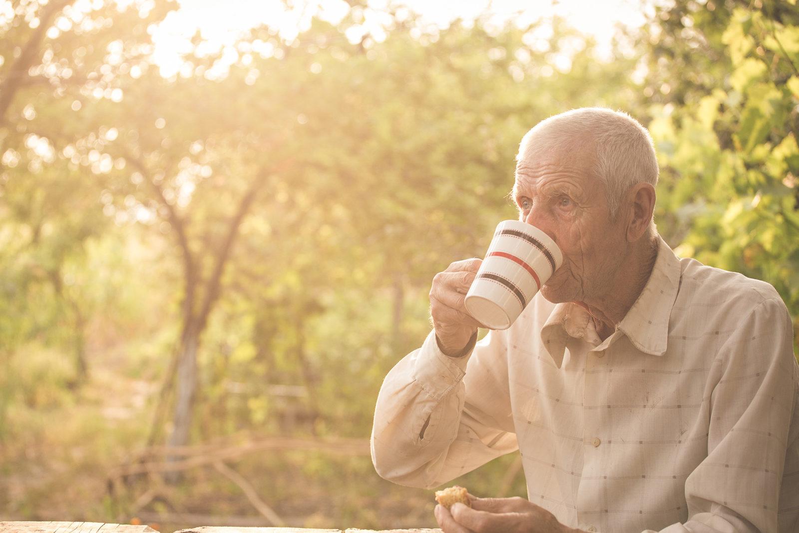 Senior man drinking a tea in his garden adjusting to retirement