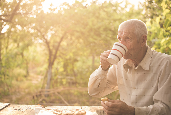 Senior man drinking a tea in his garden adjusting to retirement