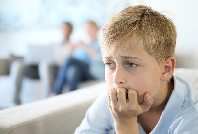 Children sat looking upset with parents in the background
