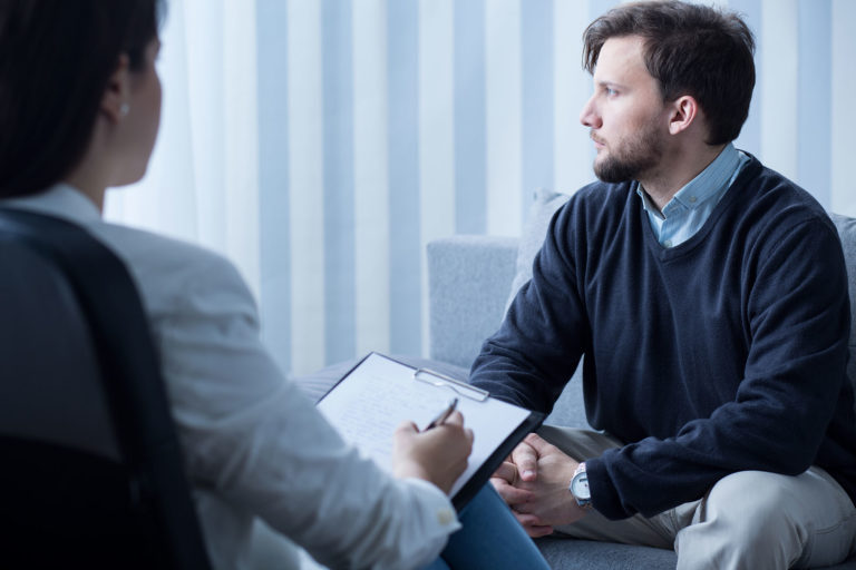 Man sitting with health professionals getting relationship advice