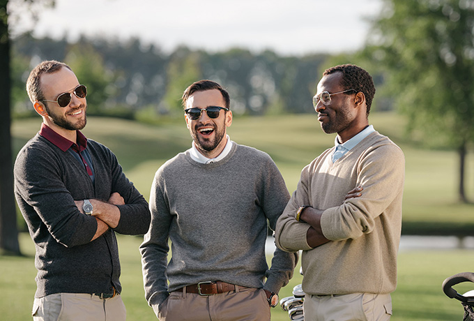 Three men playing golf discussing their mental wellbeing