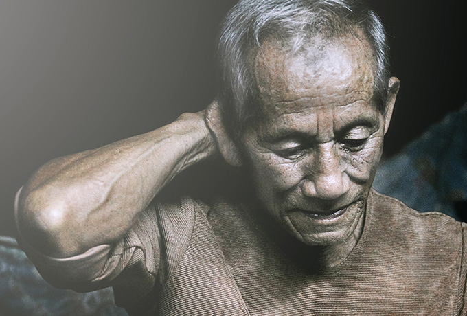 Senior Asian man depressed with head in hands
