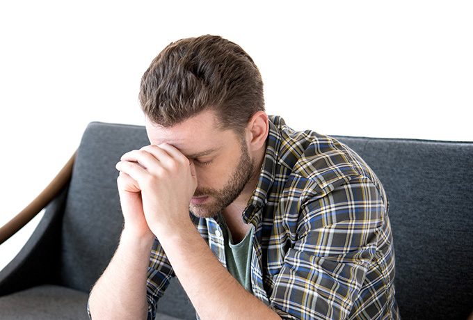 Man with head in hands thinking about the violence he uses in his relationship