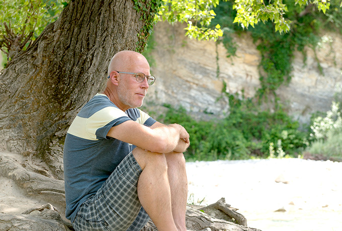Man suffering depression sitting under a tree