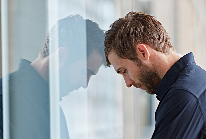 Man with head against a window feeling anxious