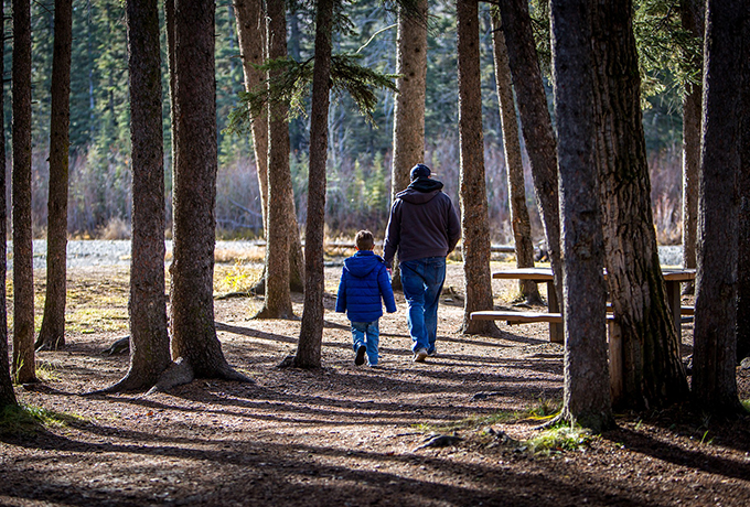 Father and son walking through the forest - having a conversation with your kids