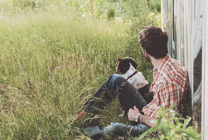 Man sat with dog in a field