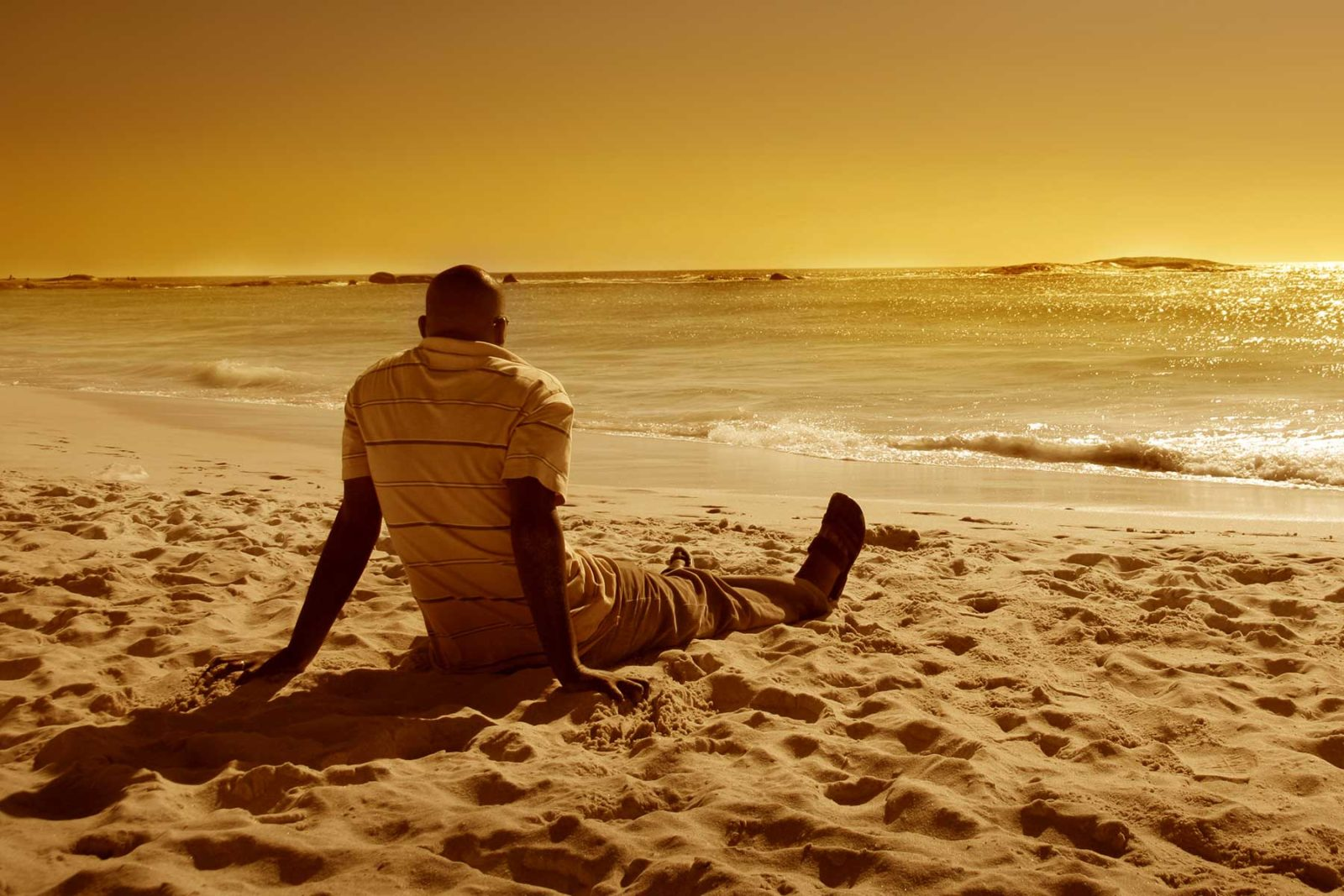 Man having a moment of mindfulness on a beach