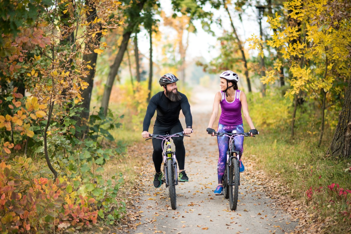Happy couple cycling through the woods