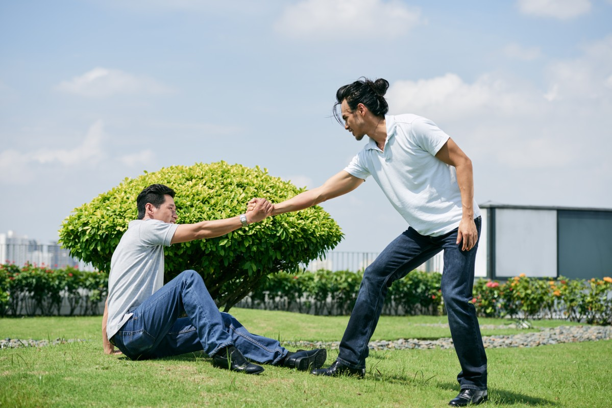 A man helping another man to his feet in a park