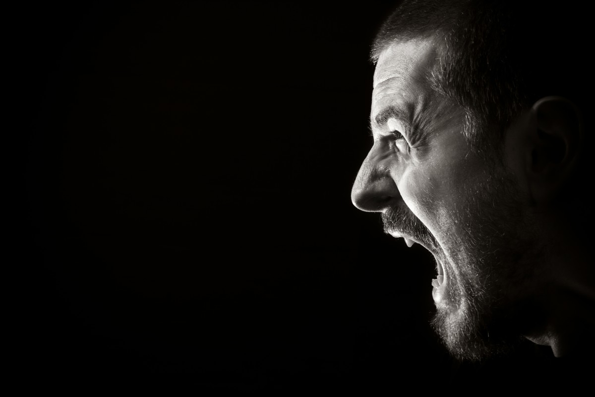 Portrait of screaming angry man on black background