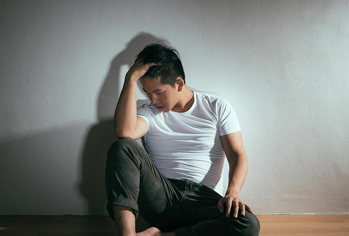An upset man sitting against a wall