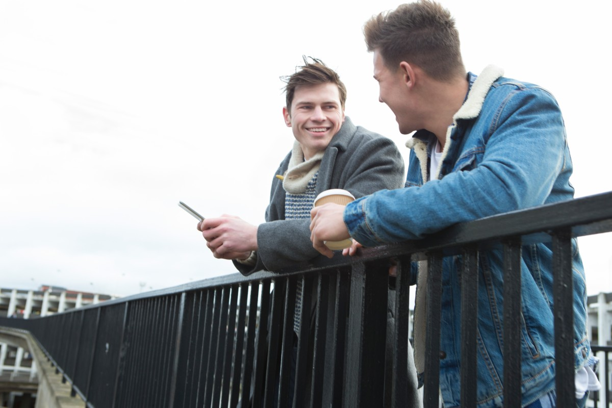 Two young men talking in the city. One is holding a smartphone, the other is holding a disposable coffee cup.