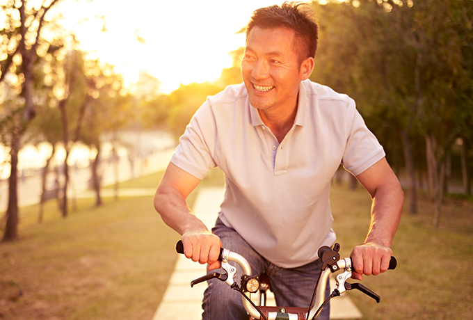 Healthy man riding his bike with sunset