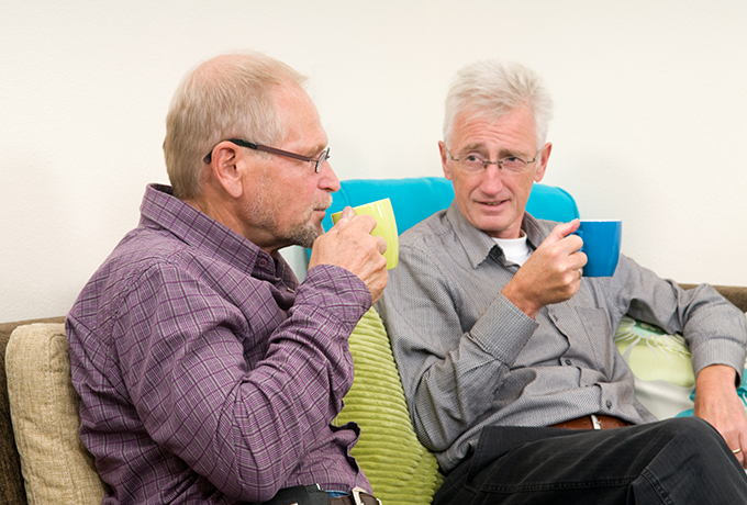 Two men sat on a couch talking drinking tea