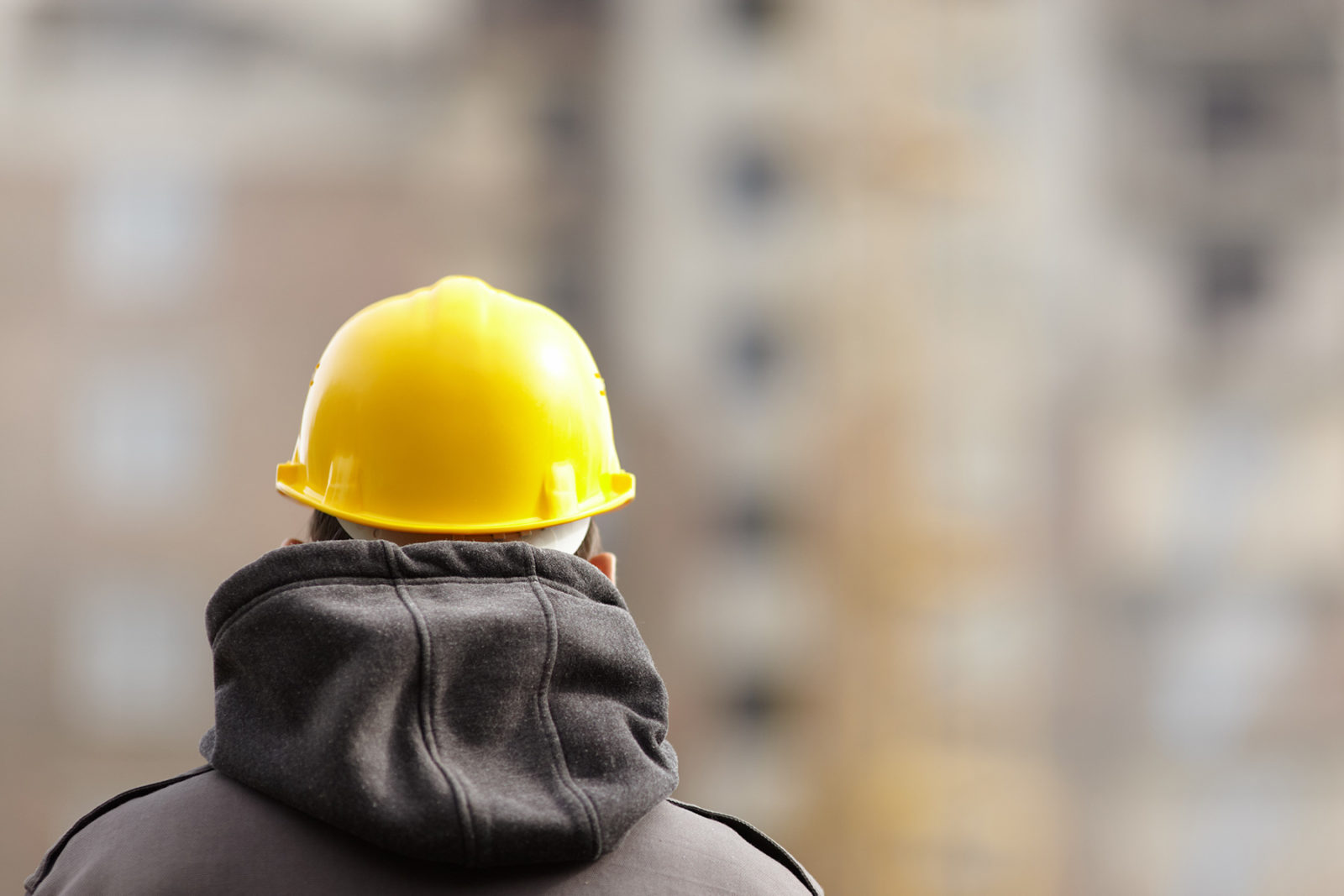 Tradie with hard hat on site thinking about mental health