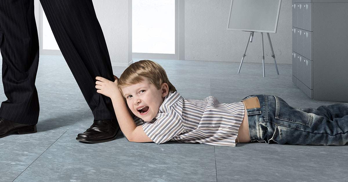Child have a tantrum holding onto Father's leg