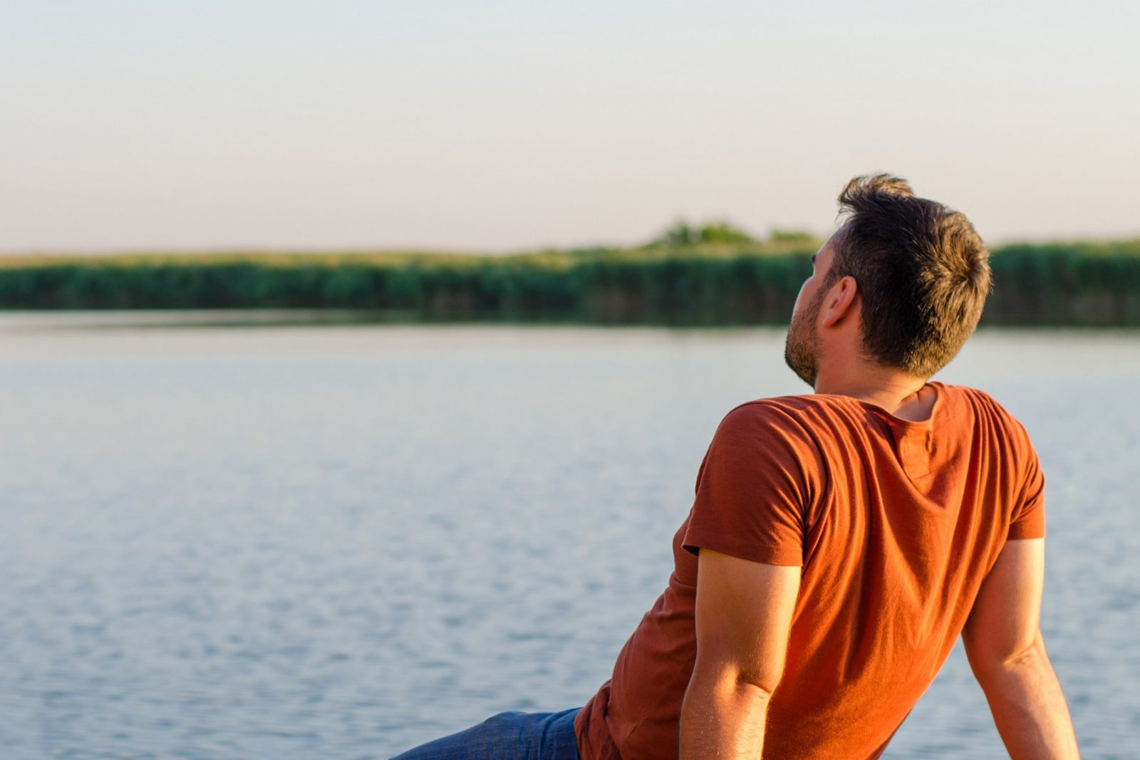 Man taking time out sitting by a lake