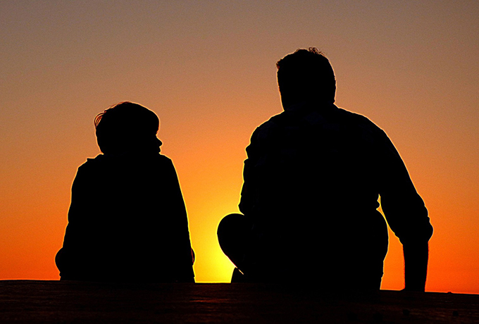 father and son sat together watching a sunset