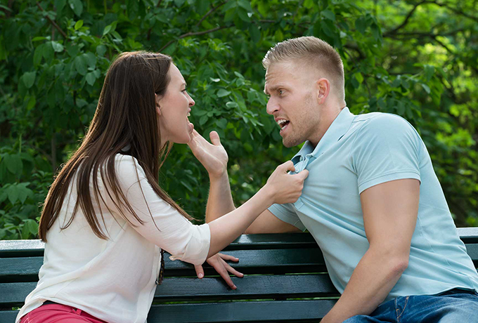 Couple sitting on a park bench arguing