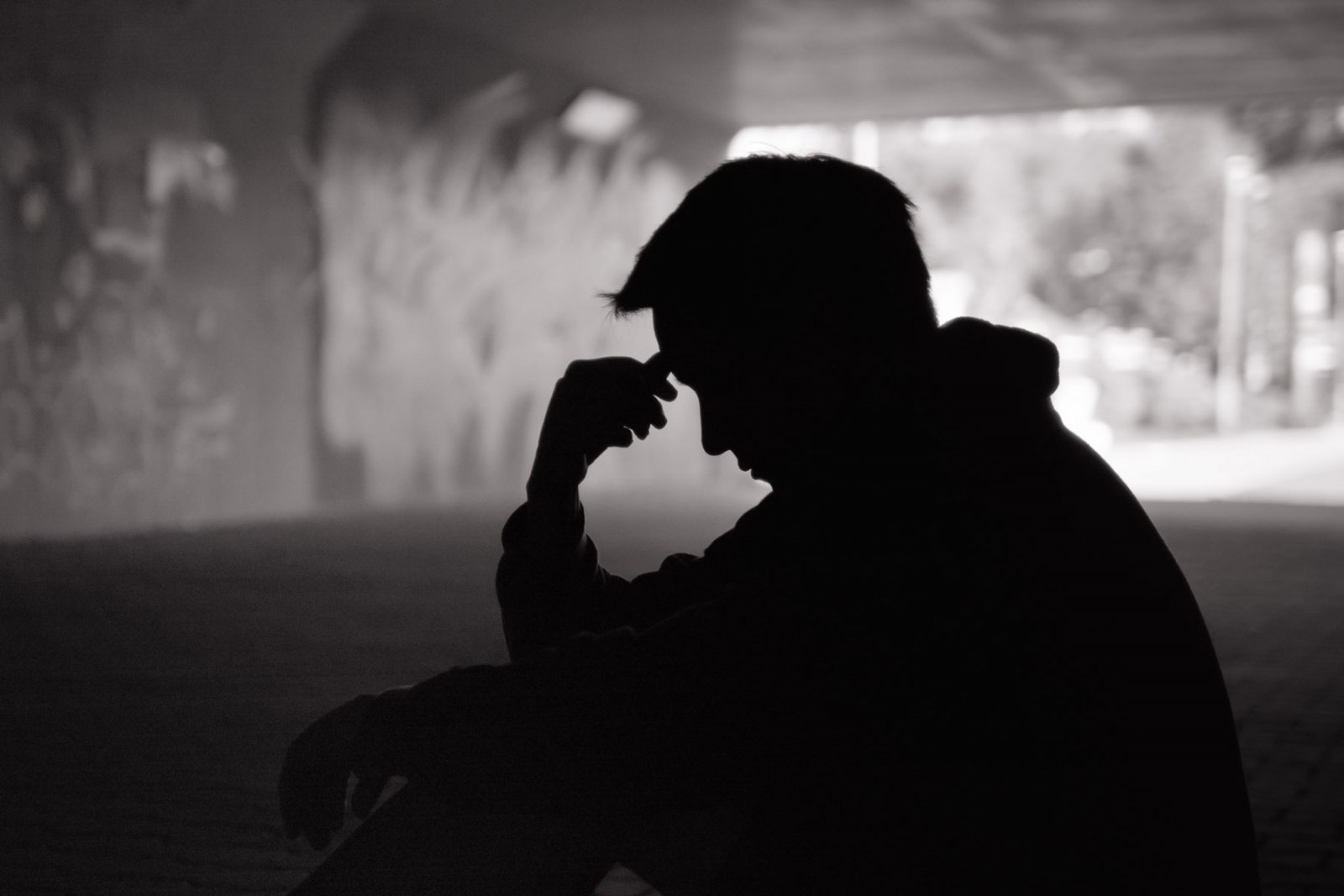 silhouette of a man sitting alone
