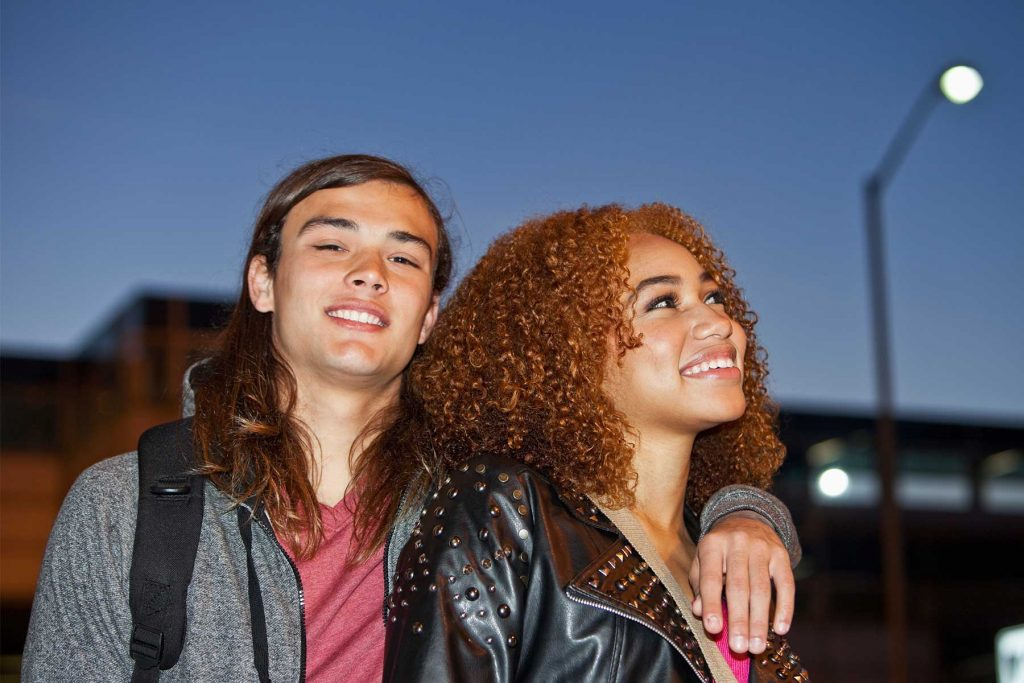 Young couple arm in arm walking at dusk