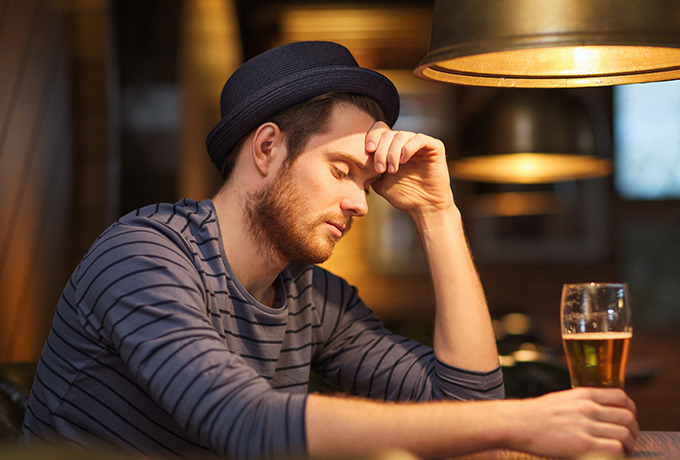 Man sitting alone at a bar drinking alcohol