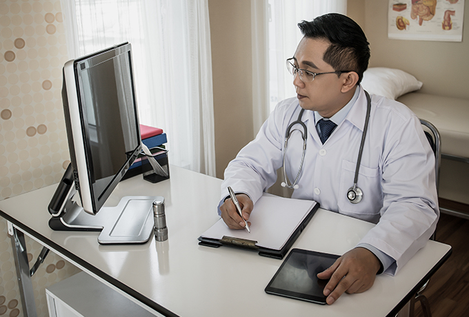 Health professional using a computer to refer a client to MensLine Australia