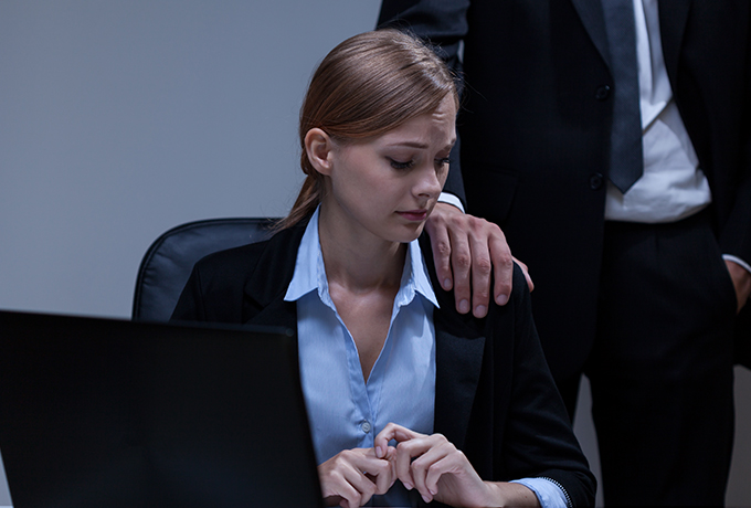 man touching a women inappropriately in an office