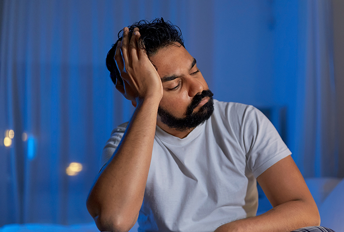 man trying to sleep suffering from burnout