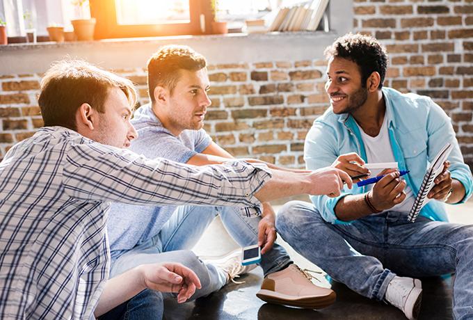 Group of men sat talking together
